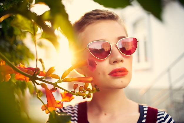 Mooie vrouw buitenshuis met zonnebril bloemen close-up
