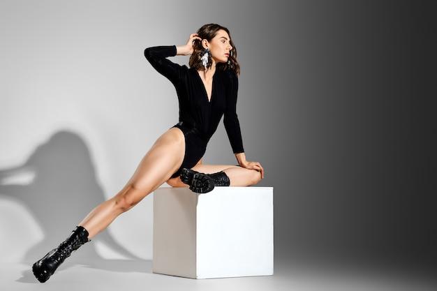 Mooie vrouw danseres zit op kubus in studio in ruwe laarzen
