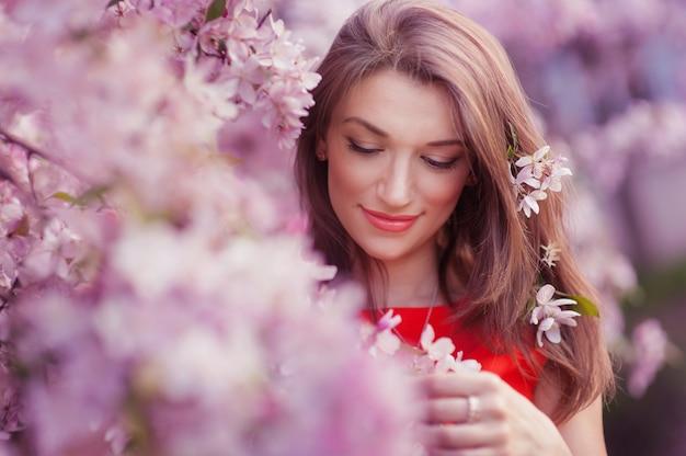Mooie vrouw dichtbij de tot bloei komende de lenteboom