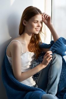 Mooie vrouw dichtbij venster binnenlandse vrije tijd blauwe plaid