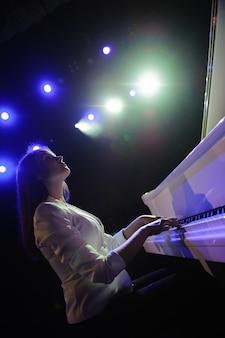 Mooie vrouw dichtbij witte piano om de scène