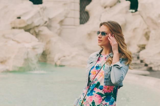 Mooie vrouw die aan de fontein van trevi kijkt