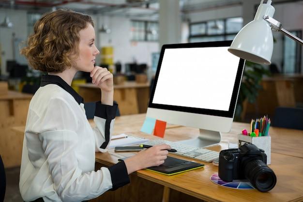 Mooie vrouw die aan desktoppc werkt