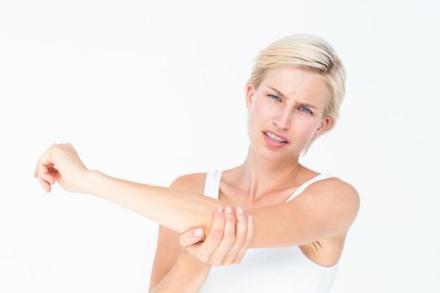 Mooie vrouw die aan elleboogpijn lijdt