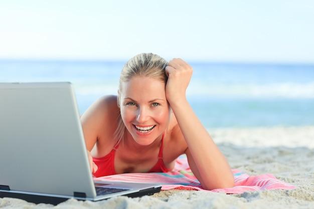 Mooie vrouw die aan haar laptop bij het strand werkt