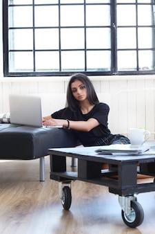 Mooie vrouw die aan haar laptop werkt