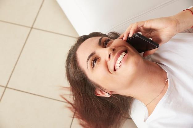 Mooie vrouw die aan mobiel op bank spreekt