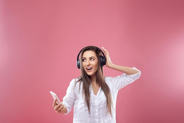 Mooie vrouw die aan muziek luistert die draadloze hoofdtelefoons gebruikt