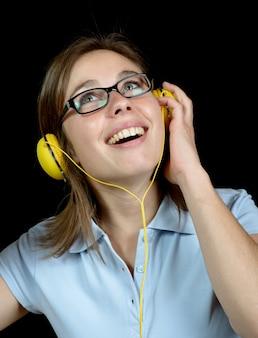 Mooie vrouw die aan muziek met een hoofdtelefoon luistert