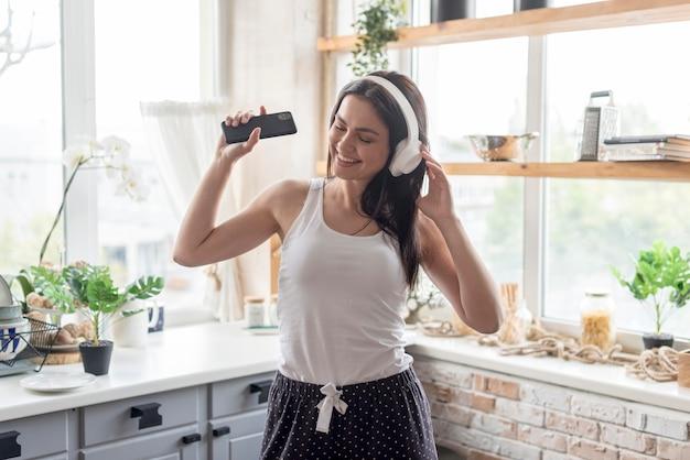 Mooie vrouw die aan muziek thuis luistert