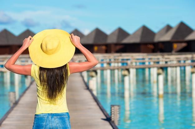 Mooie vrouw die aan waterbungalow bij tropische vakantie loopt