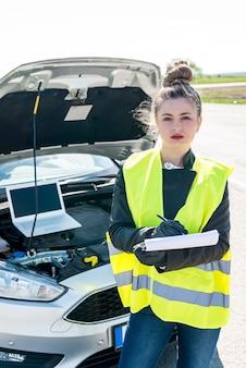 Mooie vrouw die aantekeningen maakt tijdens het diagnosticeren van de auto