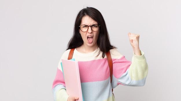 Mooie vrouw die agressief met een boze uitdrukking schreeuwt. universitair studentenconcept