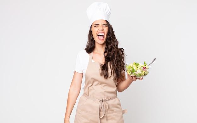 Mooie vrouw die agressief schreeuwt, er erg boos uitziet met een schort en een salade vast