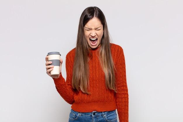 Mooie vrouw die agressief schreeuwt, erg boos, gefrustreerd, woedend of geïrriteerd kijkt, nee schreeuwt