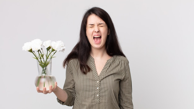 Mooie vrouw die agressief schreeuwt, erg boos kijkt en decoratieve bloemen vasthoudt. assistent-agent met een headset