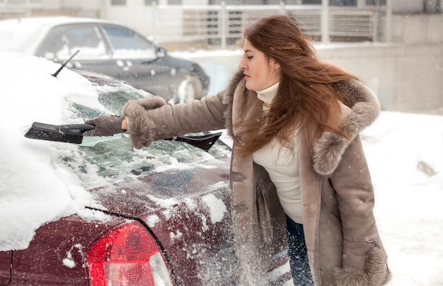 Mooie vrouw die auto schoonmaakt bij blizzard