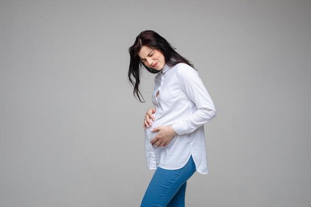 Mooie vrouw die baby verwacht, raak zwangere buik aan die pijn voelt op grijze studioachtergrond. begin van weeën