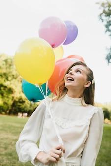 Mooie vrouw die ballons bekijkt