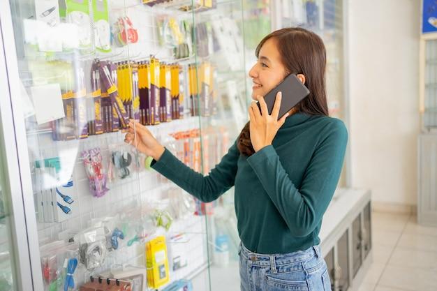 Mooie vrouw die belt met een smartphone terwijl ze mobiele telefoonaccessoires kiest in een vitrine