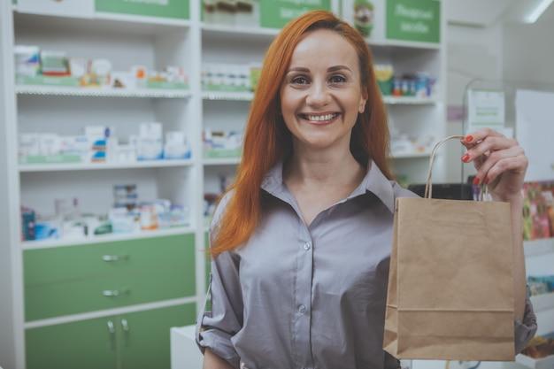 Mooie vrouw die bij de apotheek winkelt