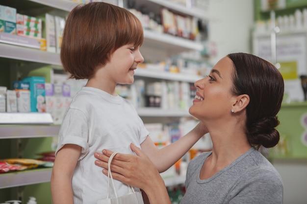 Mooie vrouw die bij drogisterij met haar kleine zoon winkelt