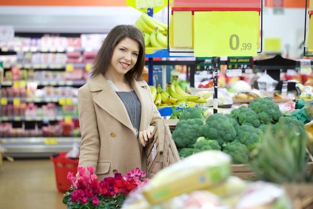 Mooie vrouw die bij supermarkt koopt