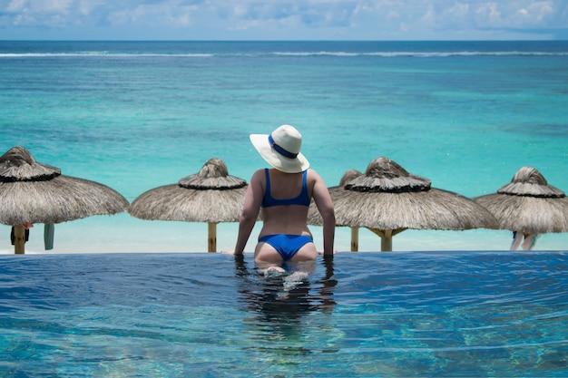 Mooie vrouw die bikini draagt die de oceaan bij oneindigheidspool bij een toevlucht bekijkt