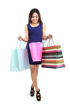 Mooie vrouw die binnen haar kleurrijke het winkelen zakken kijkt