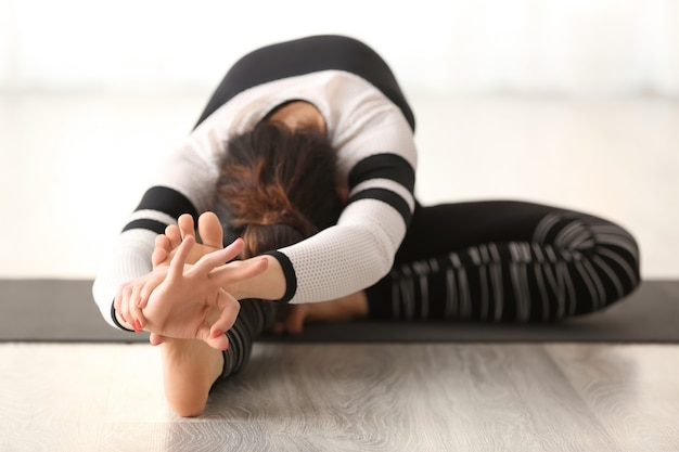 Mooie vrouw die binnen yoga beoefent
