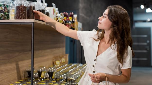 Mooie vrouw die biologische producten winkelt