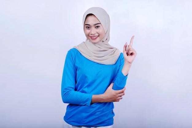 Mooie vrouw die blauw t-shirt en hijab draagt die met wijsvinger benadrukt