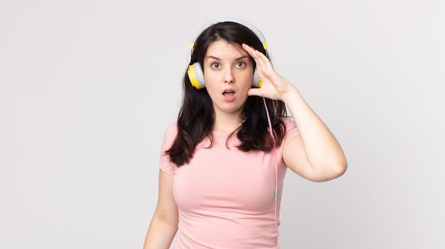 Mooie vrouw die blij, verbaasd en verrast naar muziek luistert met een koptelefoon