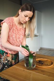 Mooie vrouw die bloemen thuis verplanten