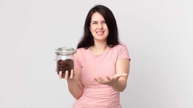 Mooie vrouw die boos, geïrriteerd en gefrustreerd kijkt en een fles koffiebonen vasthoudt