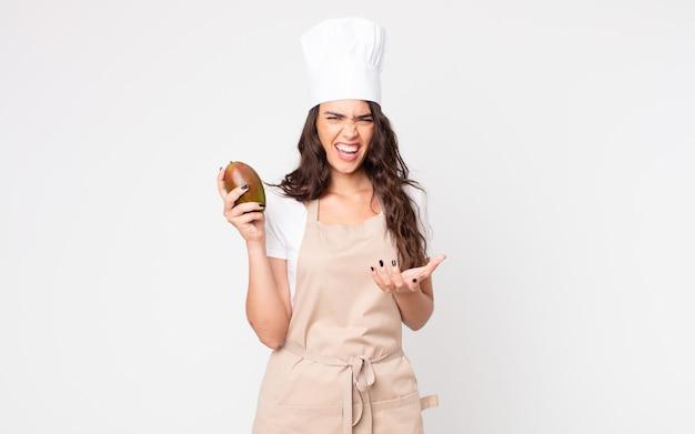Mooie vrouw die boos, geïrriteerd en gefrustreerd kijkt terwijl ze een schort draagt en een mango vasthoudt