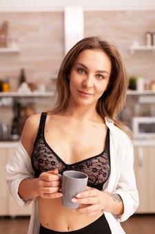 Mooie vrouw die camera in huiskeuken bekijkt die sexy lingerie draagt. jonge aantrekkelijke vrouw met tatoeages in verleidelijk ondergoed met kopje thee ontspannen in de keuken glimlachend.