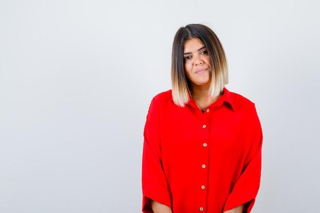 Mooie vrouw die camera in rode blouse bekijkt en delicaat, vooraanzicht kijkt.
