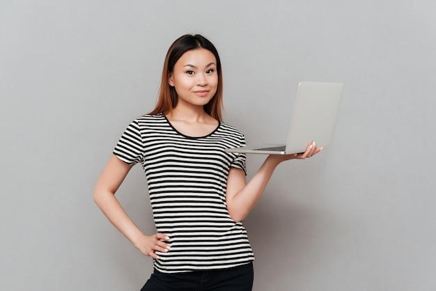 Mooie vrouw die camera kijkt terwijl het houden van laptop