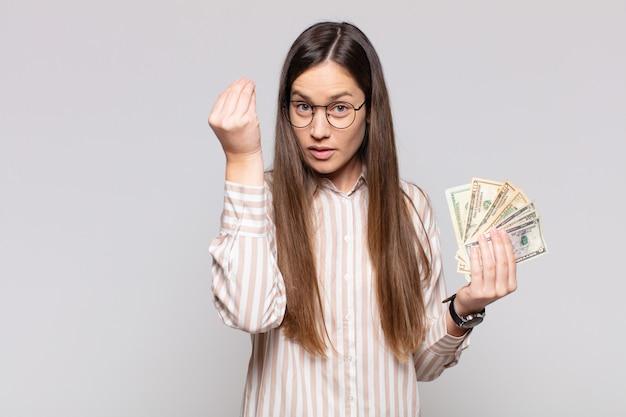 Mooie vrouw die capice of geldgebaar maakt en u vertelt uw schulden te betalen! Premium Foto