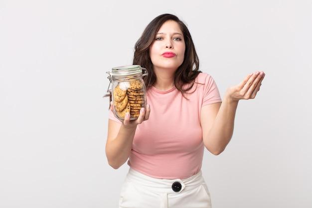 Mooie vrouw die capice of geldgebaar maakt, zegt dat je moet betalen en een glazen fles met koekjes vasthoudt