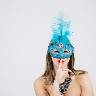Mooie vrouw die Carnaval-masker met vinger op haar lippen draagt