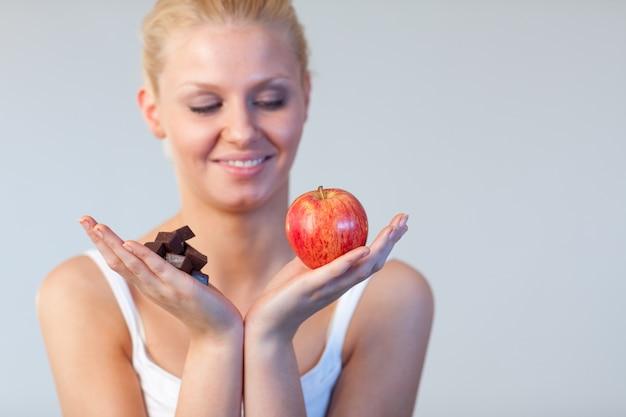 Mooie vrouw die chocolade en appeldrank op chocolade en appel toont