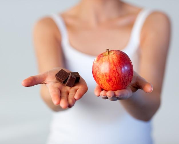 Mooie vrouw die chocolade en appelnadruk toont op chocolade
