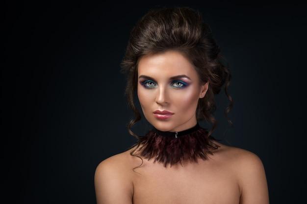 Mooie vrouw die choker draagt die van veren wordt gemaakt
