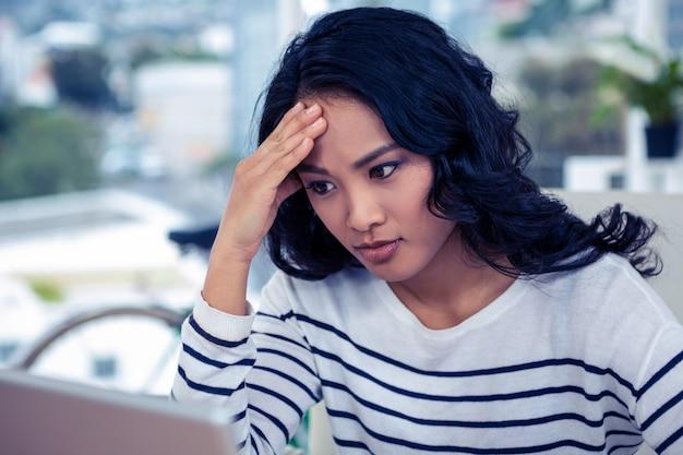 Mooie vrouw die computermonitor bekijkt met hand op hoofd in bureau