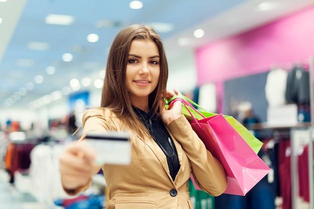 Mooie vrouw die creditcard in winkelcomplex toont