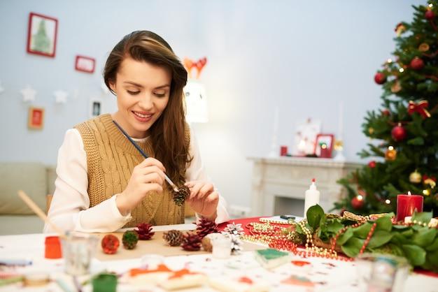 Mooie vrouw die de decoratie van kerstmis maakt