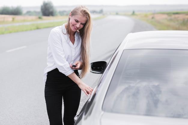 Mooie vrouw die de deur van de auto opent