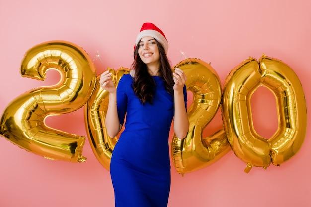 Mooie vrouw die de holdingssterretjes van de santahoed voor nieuwe jaar 2020 ballons draagt die over roze worden geïsoleerd